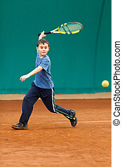 Boy playing tennis on a dross court