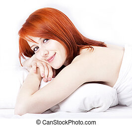 Pretty red-haired woman in white nightie lying in the bed. Photo in vogue style.