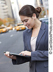 Young Woman Using Tablet Computer in New York City - A happy...