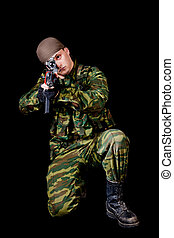 Soldier with weapon, isolated on black background