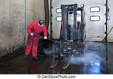 Forklift cleaning - Man cleaning a forklift using a high...