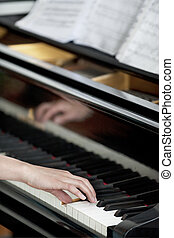 Young girl's hands on piano keyboard