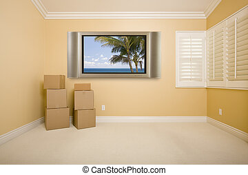 Flat Panel Television on Wall in Empty Room with Boxes -...