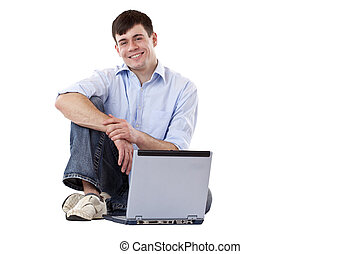 Young, handsome, casual man sitting with computer at floor...