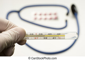 thermometer symbolizing fever - doctor is holding...
