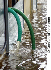 Flood water - Pipes pumping water from flooded property in...