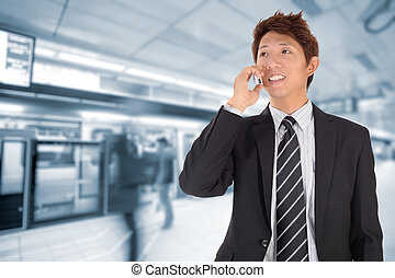 Business man using cellphone when waiting in station.