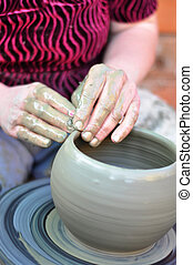 hands of a potter - The hands of a potter creating an...