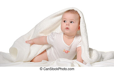 The baby under a towel. Age of 8 months. It is isolated on a...