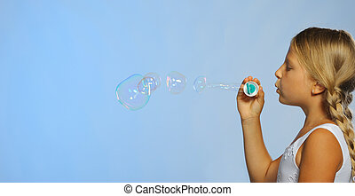 The pretty girl with soap bubbles A blue background