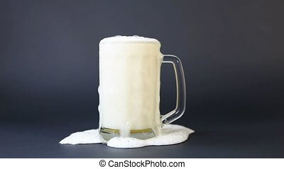 Beer foam is poured from a cup