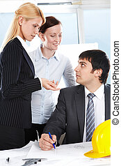 Comments - Two businesswomen asking a businessman about his...