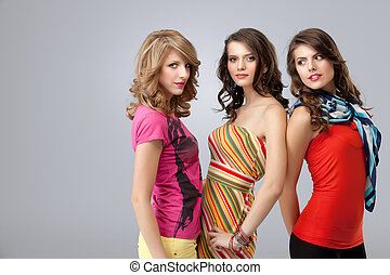 colorful studio portrait of three beautiful young women...