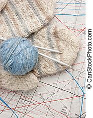 ball of yarn and mittens on a background pattern