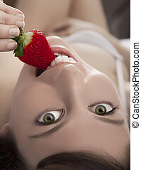 Eating fruits - Beautiful and sexy young woman lying on bed...