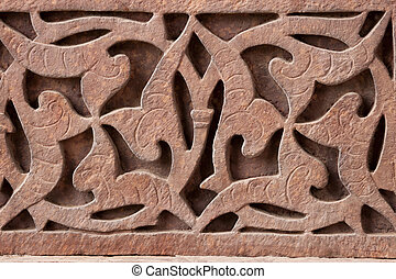 red stone carving at Qut\'b Minar. - Swastika hidden by...