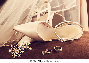 Wedding shoes with veil and rings on velvet chair