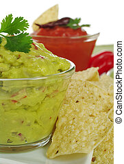 Guacamole with cilantro on top with tacos and tomato-chili...