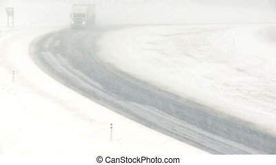 Truck in snowstorm 01 - Truck traffic on highway during a...