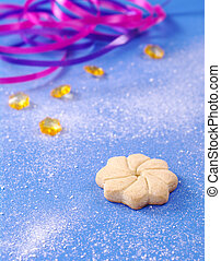Star-shaped cookie on blue with powder sugar, yellow stones, and ribbons (Selective Focus)