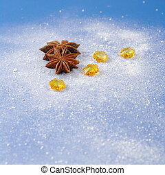 Star anise with yellow stones on blue background covered by icing sugar (Selective Focus)