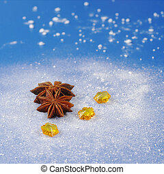 Star anise with yellow stones on blue background covered by icing sugar looking like snow (Selective Focus)