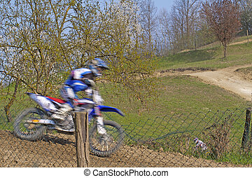 Motocross rider jumping over a dusty track in the wood