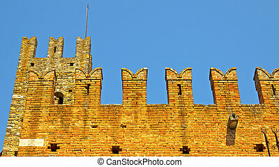 Castle - Red bricks castle with battlements under blue sky
