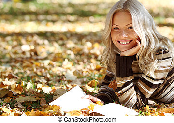 woman read in park - woman read the book in autumn park