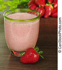 Strawberry milkshake with strawberries and leaves in the background (Selective Focus, Focus on front rim of the glass and the strawberry in front of the glass)