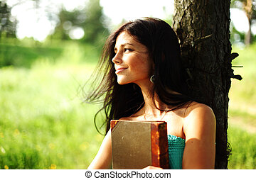 girl with book under big tree