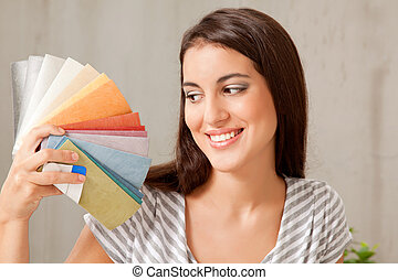 Color Swatch Pick - A young femail looking at a group of...