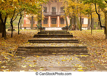 Autumn park with a footpath to a building