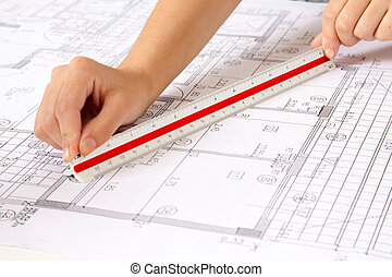 Scale Ruler on Blueprints - Two hands using a scale ruler on...