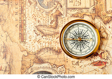 Old compass on ancient map. A compass with the antique image...
