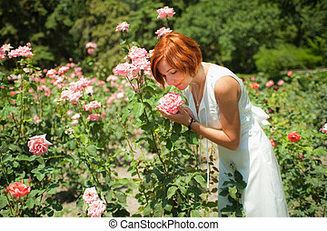woman in roses garden - Beautiful young woman in a garden of...