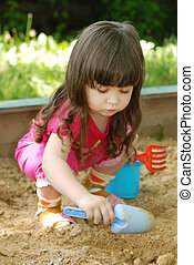 The girl playing to a sandbox. Caucasian the child, park of...