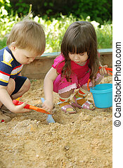 The boy and girl playing to a sandbox. Caucasian the child,...