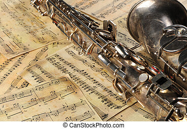Old saxophone and notes. The Musical instrument laying on...