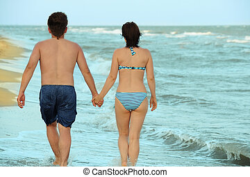 Pair on seacoast. The enamoured guy and the girl walking on...