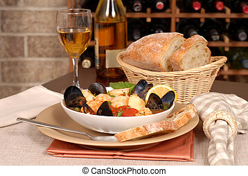 Bowl of seafood soup with wine and rustic bread - Bowl of...