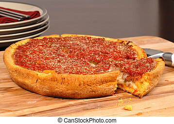 Chicago style deep dish pizza with a piece cut out - A...