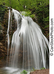 waterfall. A picturesque stream of falling water in...