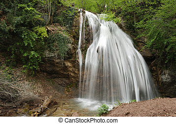 waterfall A picturesque stream of falling water in mountains...