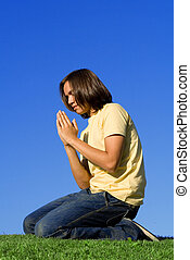christian youth kneeling and  praying