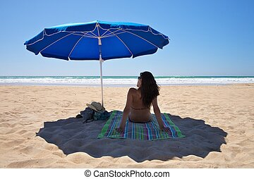 parasol with woman sit on towel - parasol at Conil Beach in...