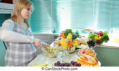 woman mixing fruit salad - Pregnant woman mixing fruit salad...
