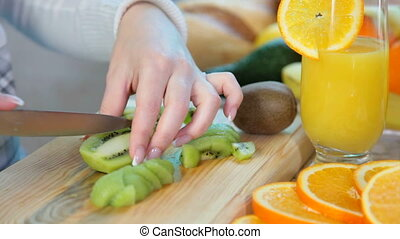 women hands slicing kiwi - women hands preparing fruit salad...