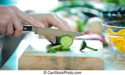 Chopping cucumber - Women hands with knife cutting cucumber...