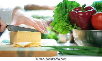 Slicing cheese - women hands slicing the cheese on the...